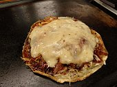 Osaka typical dish okonomiyaki with cheese on hot iron