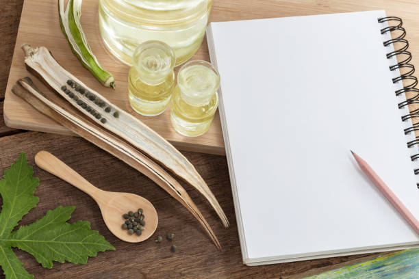 오크라 오일 이나 아벨모슈 스모렌투스 씨앗나무 배경에 노트북, 그것은 스트레스를 해소 하 고 속성 의학 개념은 성적 성능을 향상 하는 데 도움이 됩니다. 텍스트에 대한 복사 공간. 스톡 사진