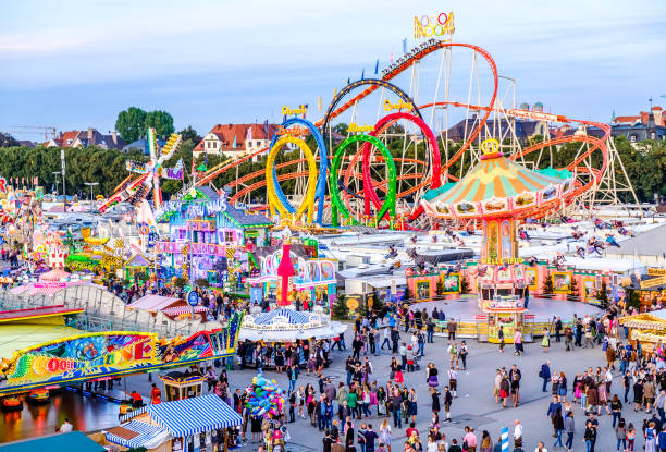 oktoberfest 2016 - munich - bavaria Munich, Germany - September 22, 2016: people and fairground rides at the biggest folk festival in the world - the octoberfest on september 22, 2016 in munich. Since 1810 it takes place on the Theresienwiese in the Bavarian state capital Munich. amusement park stock pictures, royalty-free photos & images