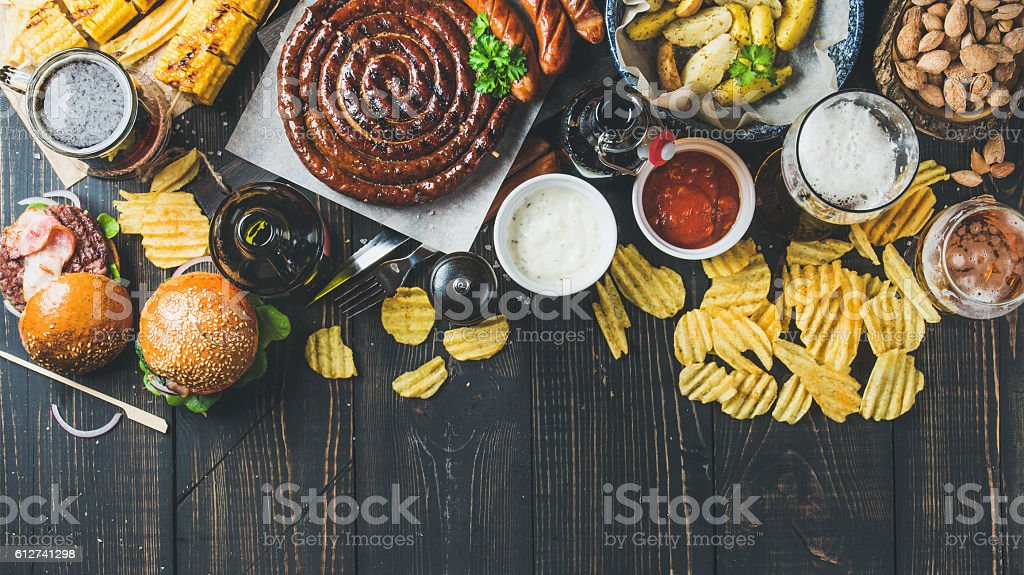 Oktoberfest beer and snacks variety on dark scorched wooden background stock photo