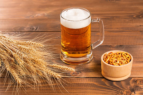 Oktoberfest Beer Mug and traditional German pretzels Oktoberfest Beer Mug and traditional German pretzels with wheat cones on the wood  table pilsner stock pictures, royalty-free photos & images