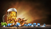 Oktoberfest beer with pretzel, wheat and hops on wooden table