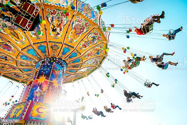 Munich, Germany - October 01, 2013: People enjoy the ride on a carousel during a sunny afternoon at the Oktoberfest in Munich (Germany). The Oktoberfest is the biggest beer festival of the world with over 6 million visitors each year.