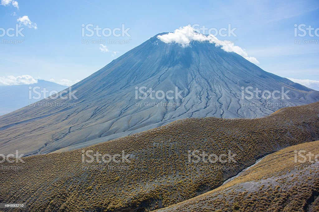 Ol Doinyo Lengai Volcano with Foothills and Clouds stock photo