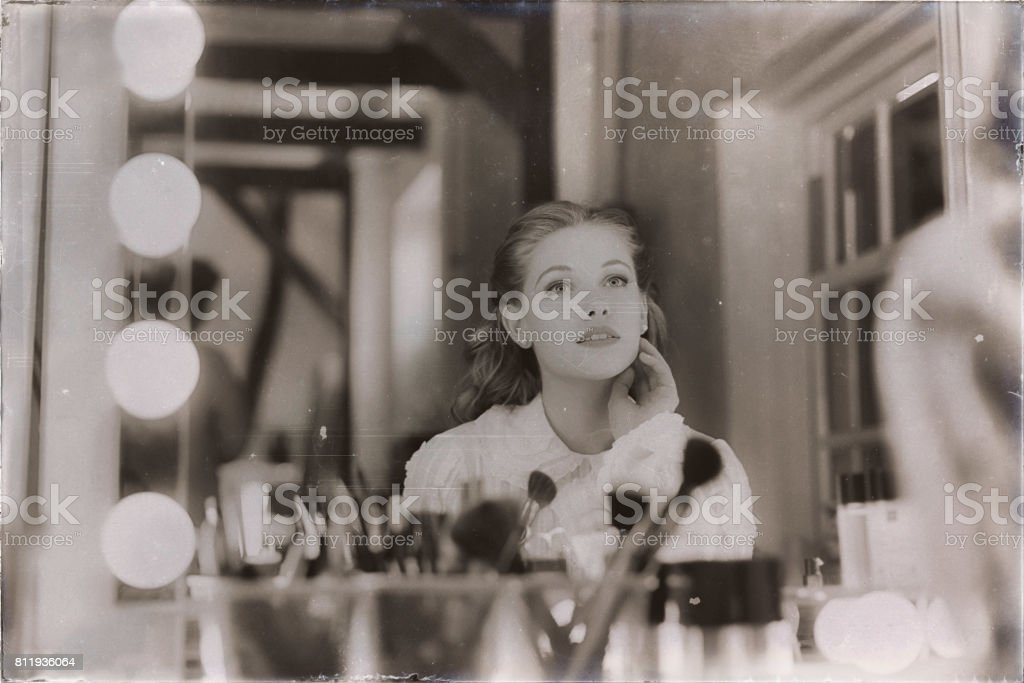 Old 1940s sepia photo of dreamy young woman looking in theater mirror. stock photo