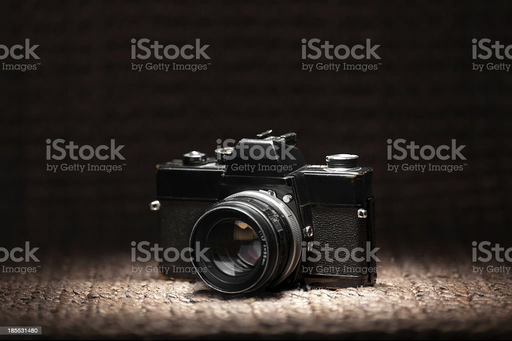 Old 35mm film camera under a spot light royalty-free stock photo