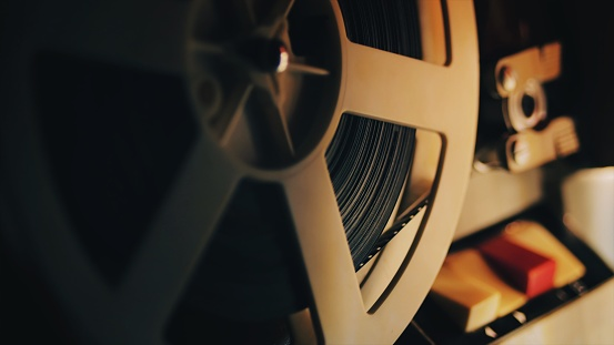 Old 8mm film projector playing in the night. Close-up of a reel with a film