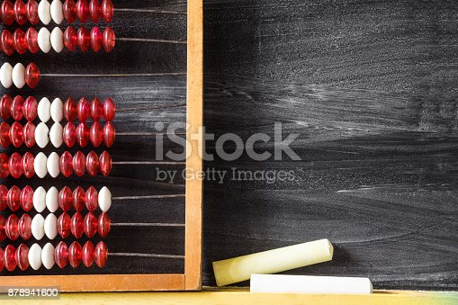 157230867istockphoto Old abacus with chalks at the blackboard in school. Mathematics lesson. Education concept. Empty place for a text. 878941600