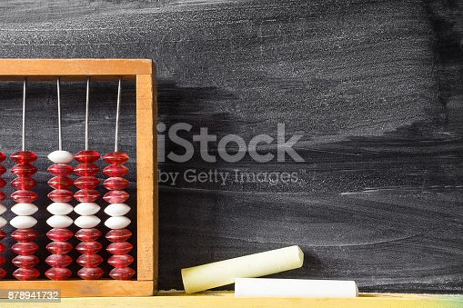 157230867istockphoto Old abacus with chalks at the blackboard in school. Mathematics lesson. Education concept. Empty place for a text. 878941732