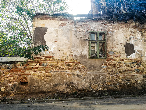 Old Abandoned And Ruined House With Smashed Window And Green