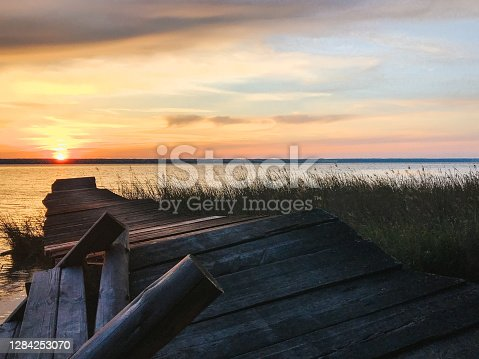 Old abandoned and ruined pier overgrown with reeds on the seashore at sunset on a summer evening