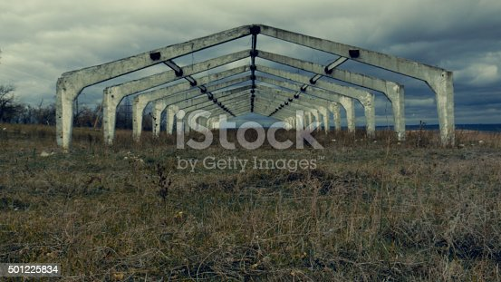 Old abandoned architectural construction at autumn field