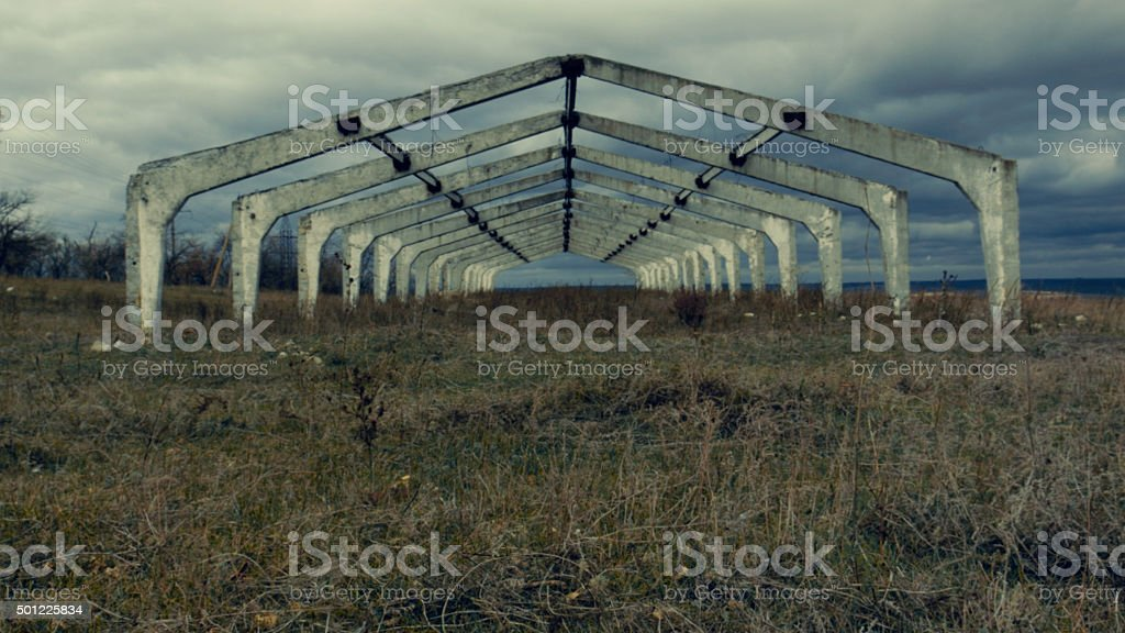 Old abandoned architectural construction at autumn field stock photo