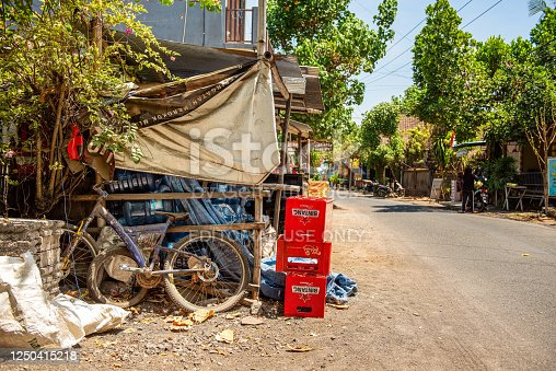 BALI, INDONESIA - December 01, 2019: Traditional Balinese Village street. Old abandoned bike and cases of beer