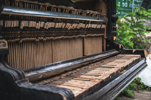 Old abandoned broken piano on the street
