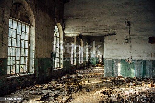 Old abandoned building with broken lancet windows inside.