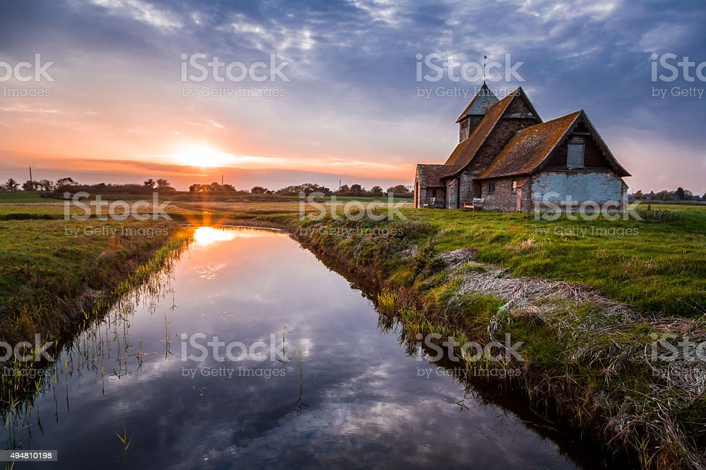 Old Abandoned Country Church at Sunset with River Reflection stock photo