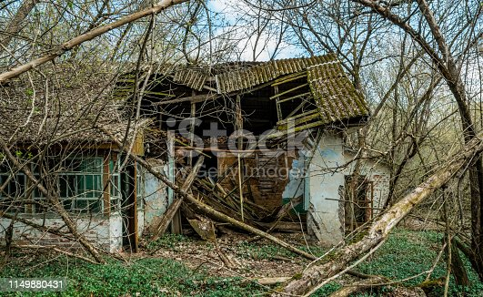 Desolation and ruin in the exclusion zone after the catastrophe at the Chernobyl nuclear power plant. Old abandoned village house in the middle of the forest