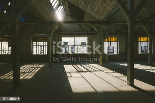 Old, abandoned factory warehouse. Photo is taken with dslr camera and wide angle lens in samo abandoned factory in Europe. Lens flare slightly visible. Kodak portra filter applied in post processing.