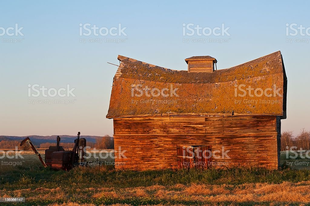 old abandoned farm building and antique machine royalty-free stock photo