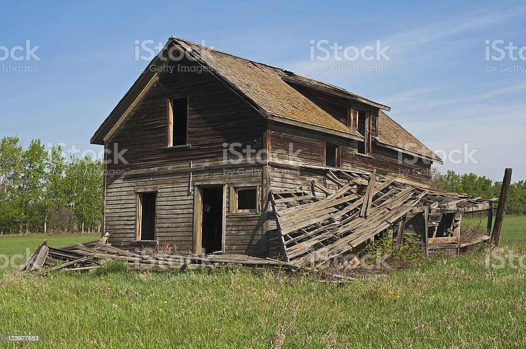 Old abandoned farm building: Derelict house with collapsed porches royalty-free stock photo