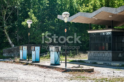 Old abandoned vintage obsolete petrol fuel gas dispensers in former neglected petrol station