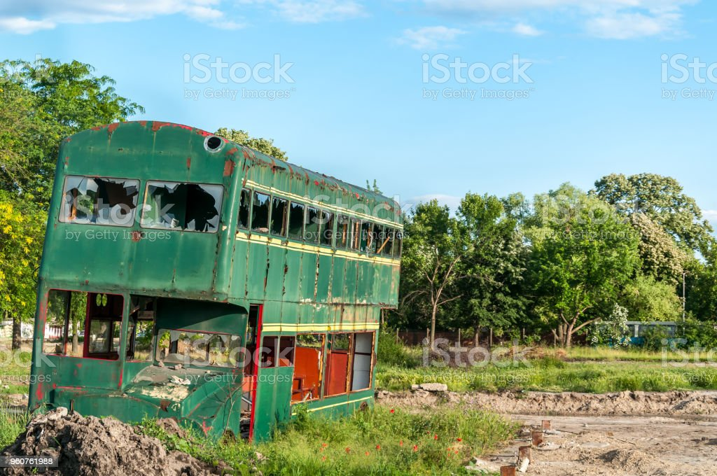Old abandoned green double decker bus with broken and shattered window glass, damaged and left to rust stock photo