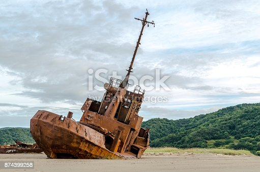 istock Old abandoned ship, standing on the sandy beach in cloudy weather. 874399258