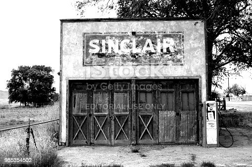 Genola, Utah, USA - 24 June 2004: Old abandoned Sinclair service station in rural Utah. Old gas pump next to the shuttered building. Black and white photo.