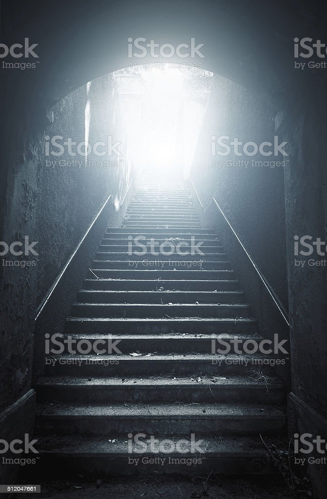 Old abandoned stairs going up to the light. Hope concept stock photo