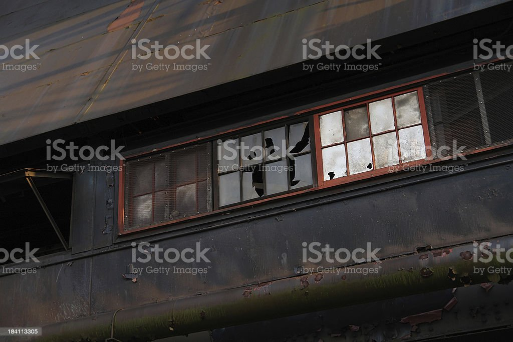 Old abandoned steel mill wall with broken windows stock photo