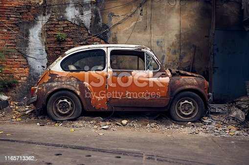 Old abandoned rusty white/orange vintage car wreck in an old street