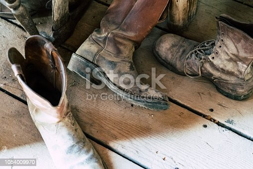 Old abandoned vintage cowboy boots sit on a dusty wooden plank floor. Selective focus for artistic purposes