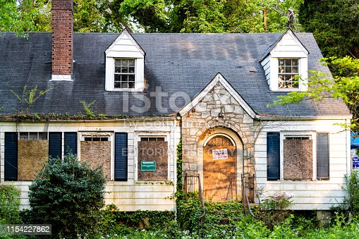 Atlanta, USA - April 21, 2018: Old abandoned weathered wooden house with entrance and notice sign warning and company buying for cash and number