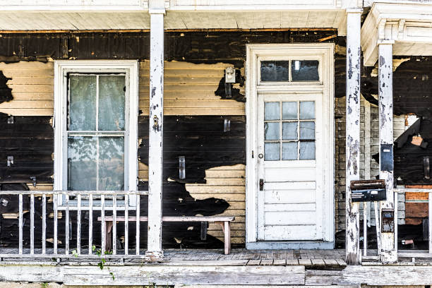 Old abandoned weathered wooden house with porch entrance, peeling paint, dirty windows stock photo