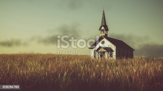 Old abandoned white wooden chapel on prairie at sunset with cloudy sky.