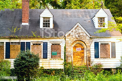Atlanta, USA - April 21, 2018: Old abandoned weathered yellow wooden house with entrance and notice sign warning and company buying for cash and number