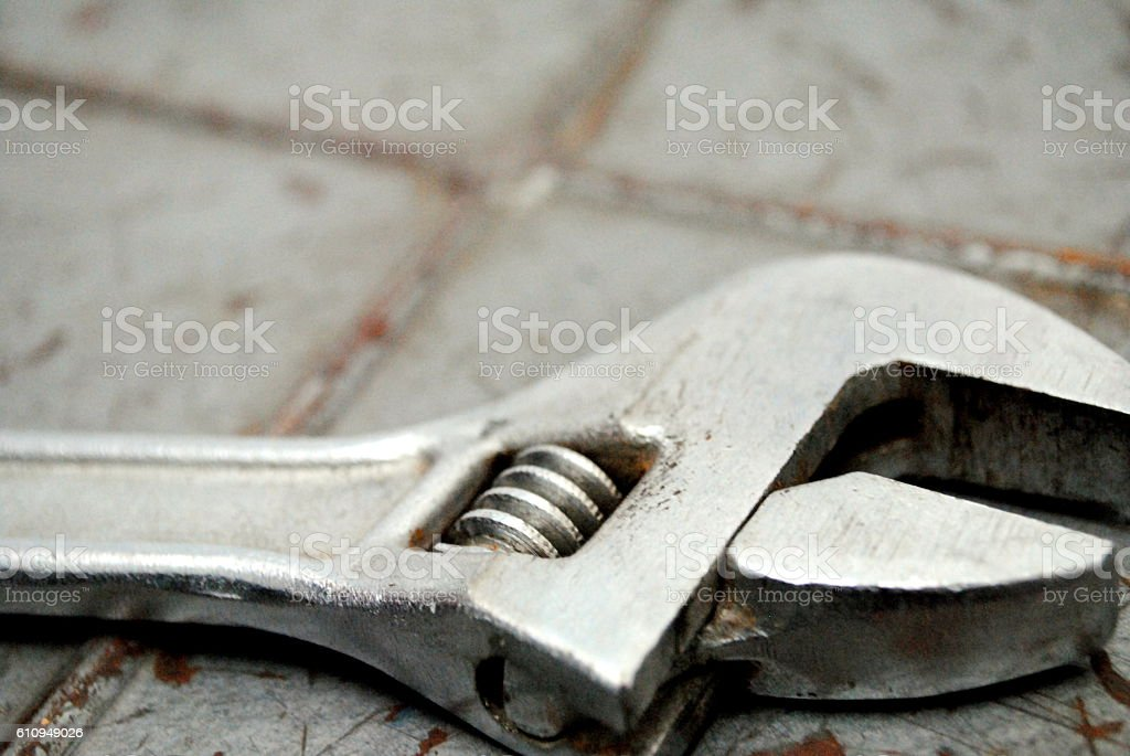 Old adjustable wrench on a rusty scratched metal stock photo