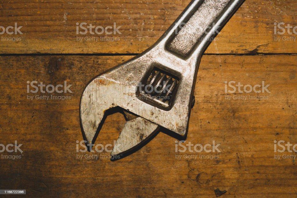 Old adjustable wrench on wood background. working tool. plumbing...