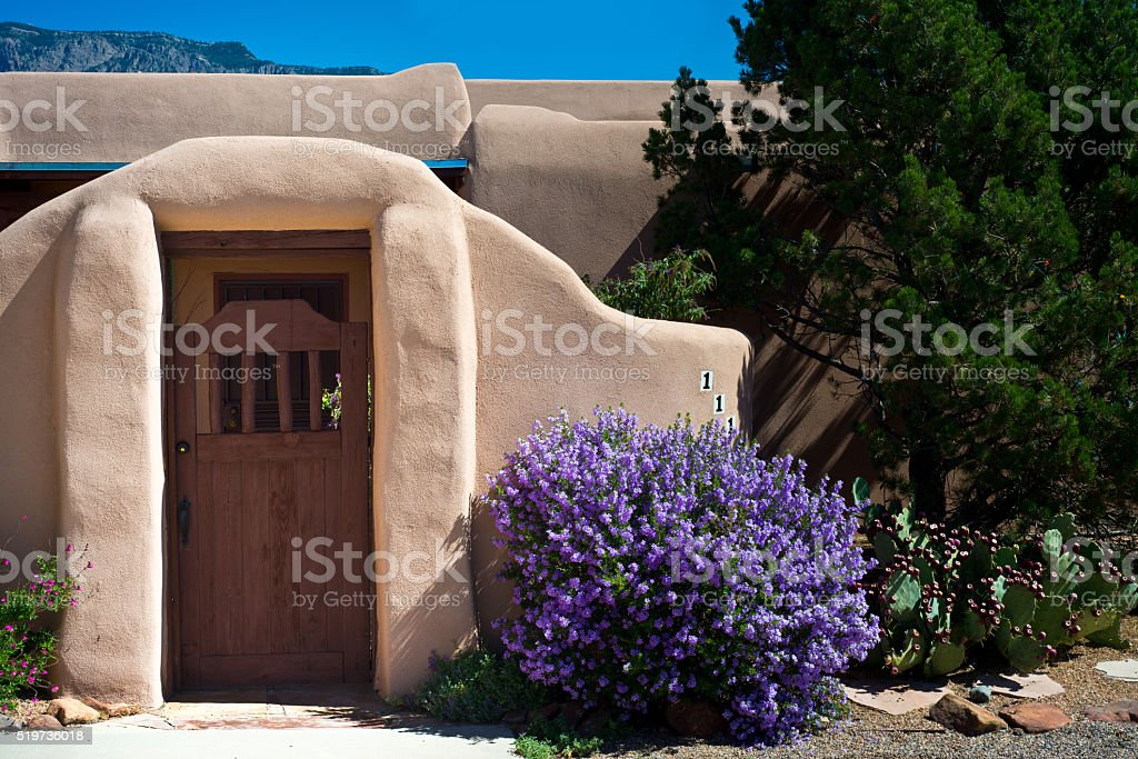 Old Adobe House with Stucco Wall and Flowers stock photo