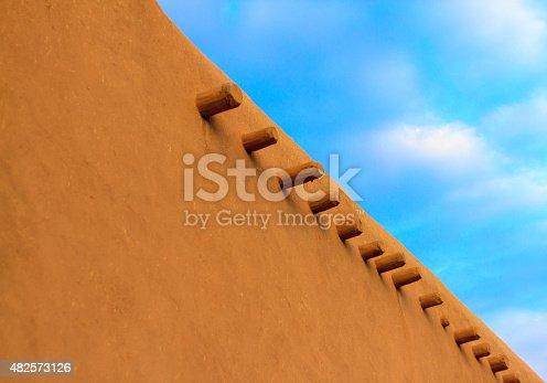An old adobe wall and vigas---the side view of Ranchos de Taos church (San Francisco de Asis Mission Church) in early morning light. Completed in 1816, the church is located near Taos, New Mexico. Copy space available.