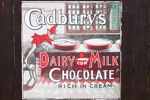 Old Advertisement for Cadbury's Dairy Milk Chocolate Glasgow, UK - September 30, 2011: An old advertisement from the 1920s attached to a wooden hoarding advertising Cadbury's Dairy Milk Chocolate. theasis stock pictures, royalty-free photos & images