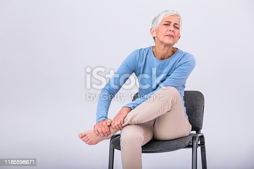 698466046 istock photo Old age, health problem and people concept - senior woman suffering from pain in leg at home. Senior woman holding her foot with pain. 1185598671