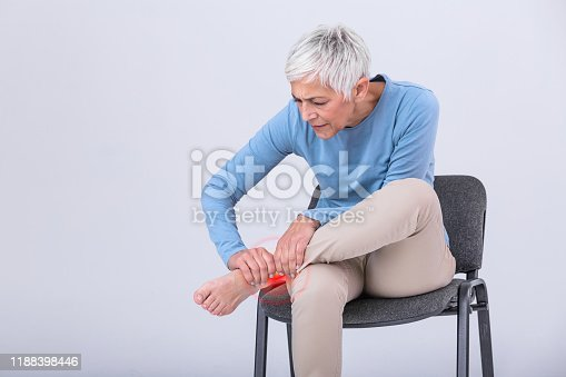 698466046 istock photo Old age, health problem and people concept - senior woman suffering from pain in leg at home. Senior woman holding her foot with pain. 1188398446