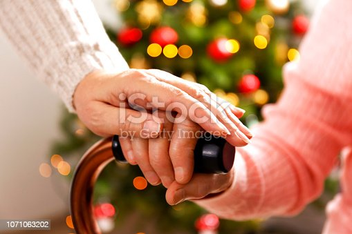 Elderly woman celebrating Christmas at home, with decorated holiday pine tree on background. Old lady at nursing home. Close up, copy space, cropped shot.