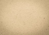 Old aged beige brown particle pressed wood panel of oriented strand board (OSB) texture background in light cream sepia color