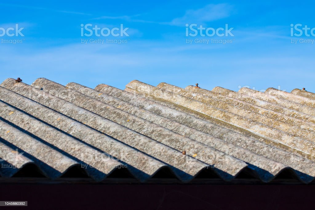 Old aged dangerous asbestos roof made of concrete panels - one of the most dangerous materials in buildings so-called 'u2018hidden killer'u2019 stock photo