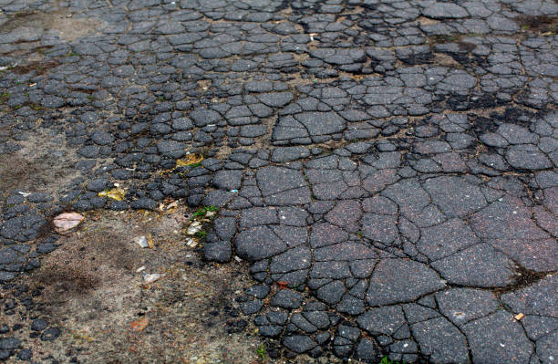Old aged grey cracked asphalt road surface stock photo