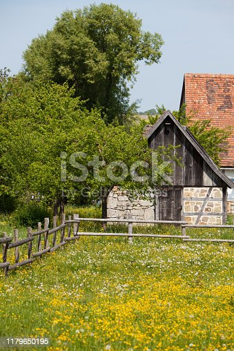 Old agricultural barn building with trees and a wildflower meadow