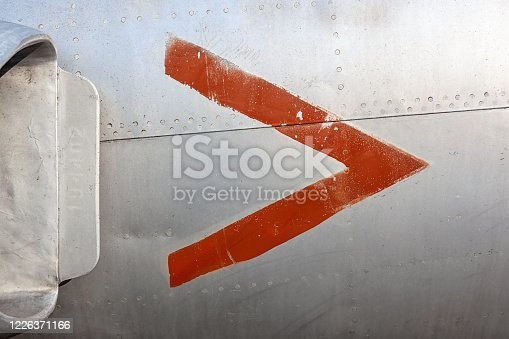 487808089 istock photo Old aircraft aluminum panel with red arrow. 1226371166